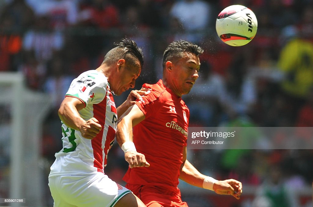 Fernando Uribe (R) of Toluca jumps for the ball with Mario de Luna of Necaxa during their Mexican Apertura football tournament match at the Nemesio Diez stadium in Toluca, Mexico, on August 20, 2017. /