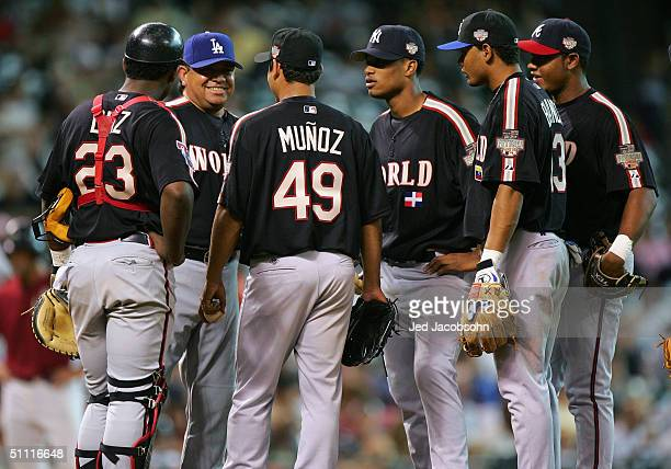 Fernando Valenzuela of the World team pays a visit to the mound to talk to players Robinzon Diaz Arnaldo Munoz Robinson Cano Andres Blanco and Andy...