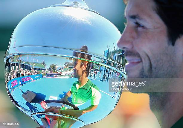 Fernando Verdasco of Spain is reflected in the trophy as he holds it after defeating Alexandr Dolgopolov of Ukraine in the Championship Match to win...