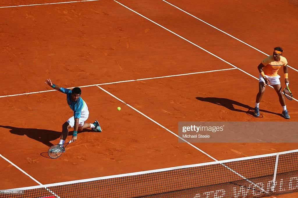 Fernando Verdasco (L) of Spain makes a return as Rafael Nadal (R) of Spain looks on in the doubles against Philipp Kohlschreiber of Germany and Viktor Troicki of Serbia during day two of the Monte Carlo Rolex Masters at Monte-Carlo Sporting Club on April 11, 2016 in Monte-Carlo, Monaco.