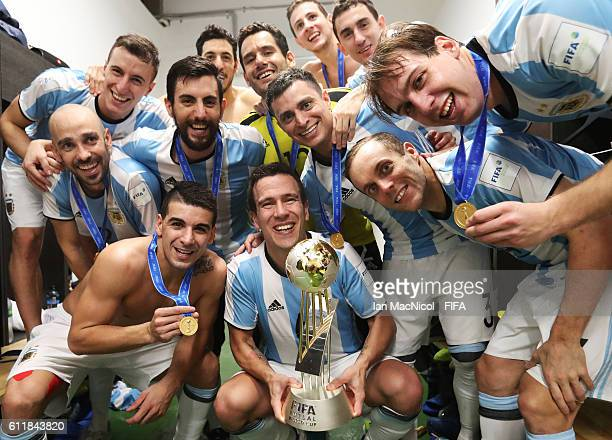Fernando Wilhelm of Argentina poses with the winners trophy during the FIFA Futsal World Cup Final match between Russia and Argentina at the Coliseo...