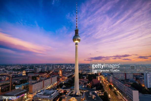 fernsehturm amidst illuminated city at night - berlin stock pictures, royalty-free photos & images