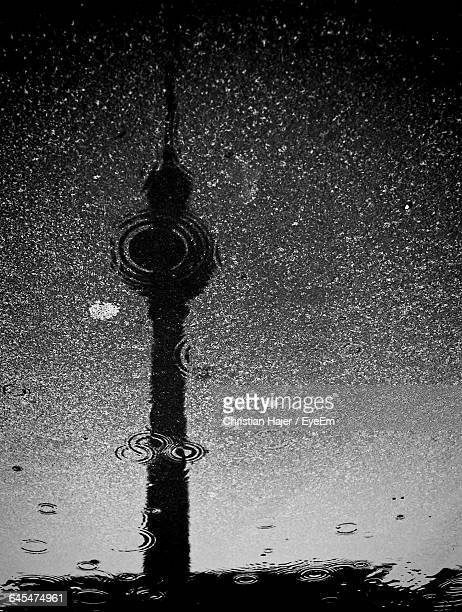 Fernsehturm Reflecting In Puddle On Street During Monsoon