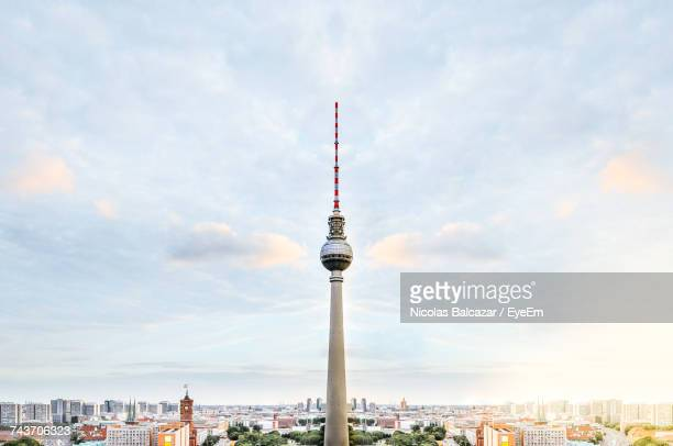 Fernsehturm Tower And Buildings Against Cloudy Sky In City