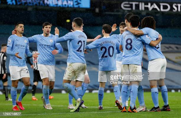 Ferran Torres of Manchester City celebrates with teammates Joao Cancelo and Ruben Dias after scoring his team's second goal during the Premier League...