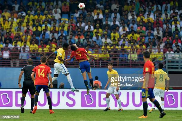 Ferran Torres of Spain and Vitao of Brazil jump for the ball during their group stage football match in the FIFA U17 World Cup played at the...