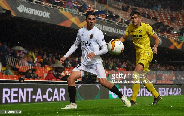 Ferran Torres of Valencia competes for the ball with Andrei Ratiu of Villarreal during the UEFA Europa League Quarter Final Second Leg match between...