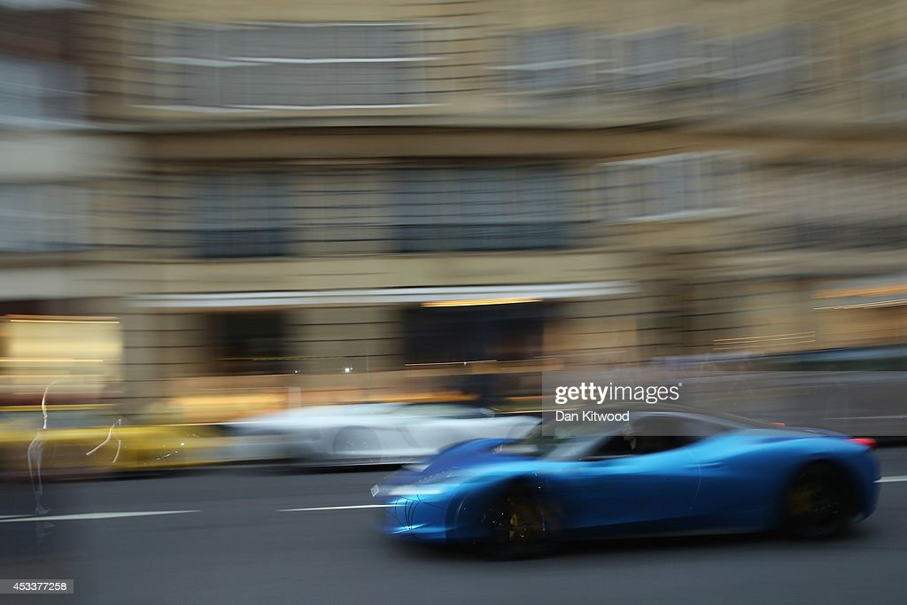 A Ferrari 456 Italia drives down Sloane Street in Knightsbridge on August 8, 2014 in London, England. Tourists and car enthusiasts have been flocking to the wealthy London district to see some of the world's most expensive and extravagant super cars. Many of the rich owners from Saudi Arabia and Kuwait come to London to escape the summer heat at home and to show off their cars before moving on to other European cities such as Paris and Cannes.