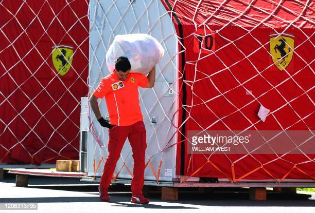 Ferrari crew member carries a bag as the Italian Formula One team unpack their equipment at the Albert Park circuit in Melbourne on March 10 ahead of...