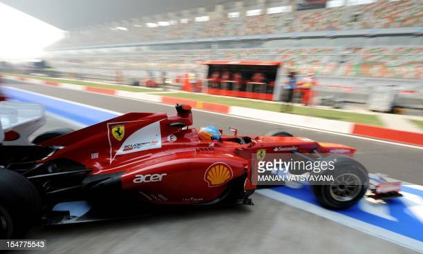 Ferrari driver Fernando Alonso of Spain drives out of the pit during the first practice session at the Buddh International circuit in Greater Noida,...