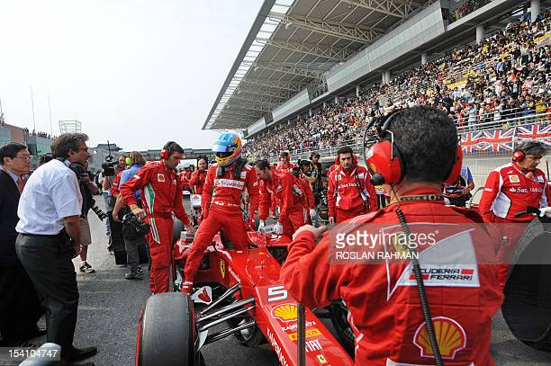 Ferrari driver Fernando Alonso of Spain gets out of his race car on the grid lane while waiting for the start of the Formula One Korean Grand Prix at...