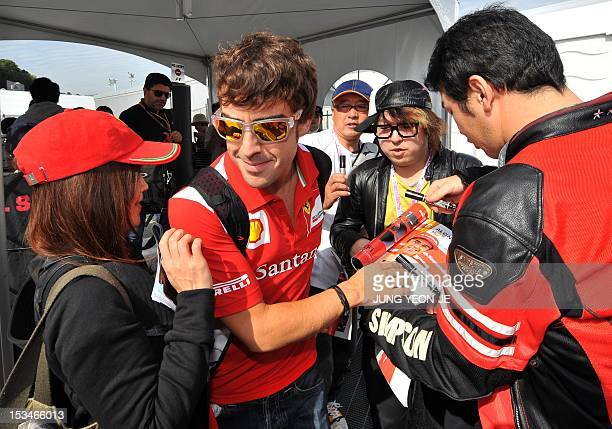 Ferrari driver Fernando Alonso of Spain is surrounded by fans as he arrives at the paddock during the Formula One Japanese Grand Prix at the Suzuka...