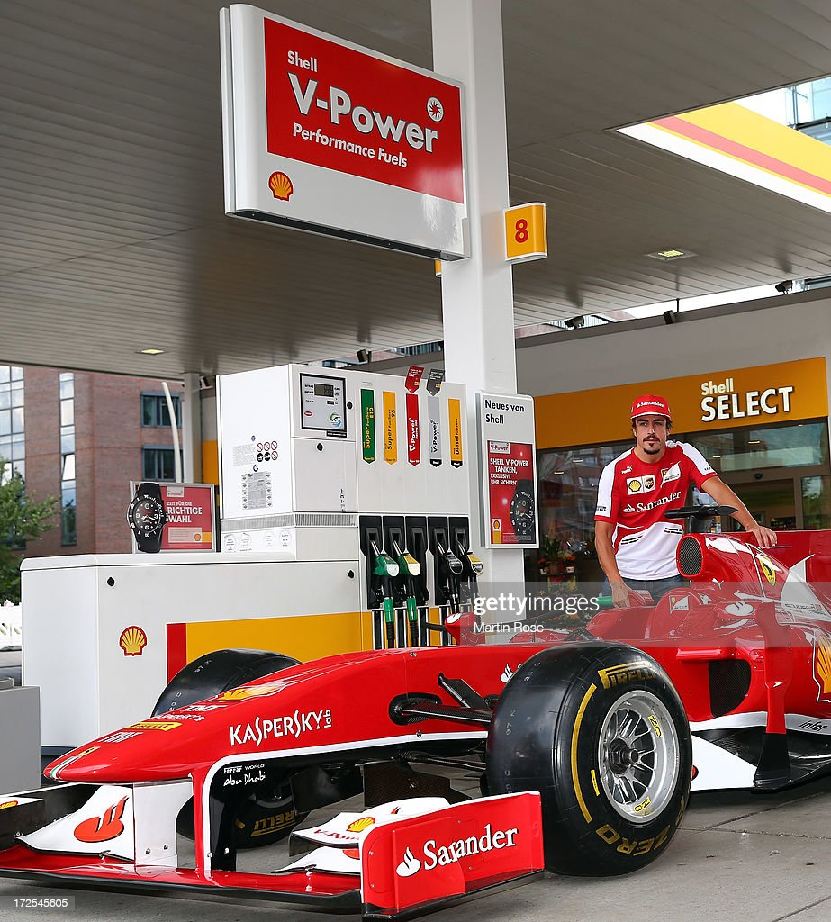 Ferrari driver Fernando Alonso of Spain pose for a photo at Shell filling station on July 3, 2013 in Hamburg, Germany.