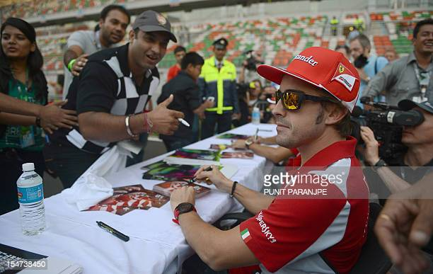 Ferrari driver Fernando Alonso of Spain poses for a fans during an autograph session at The Buddh International circuit in Greater Noida on the...
