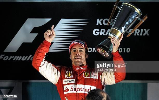 Ferrari driver Fernando Alonso of Spain raises his trophy on the podium following the South Korean Formula One Grand Prix at the Korean International...