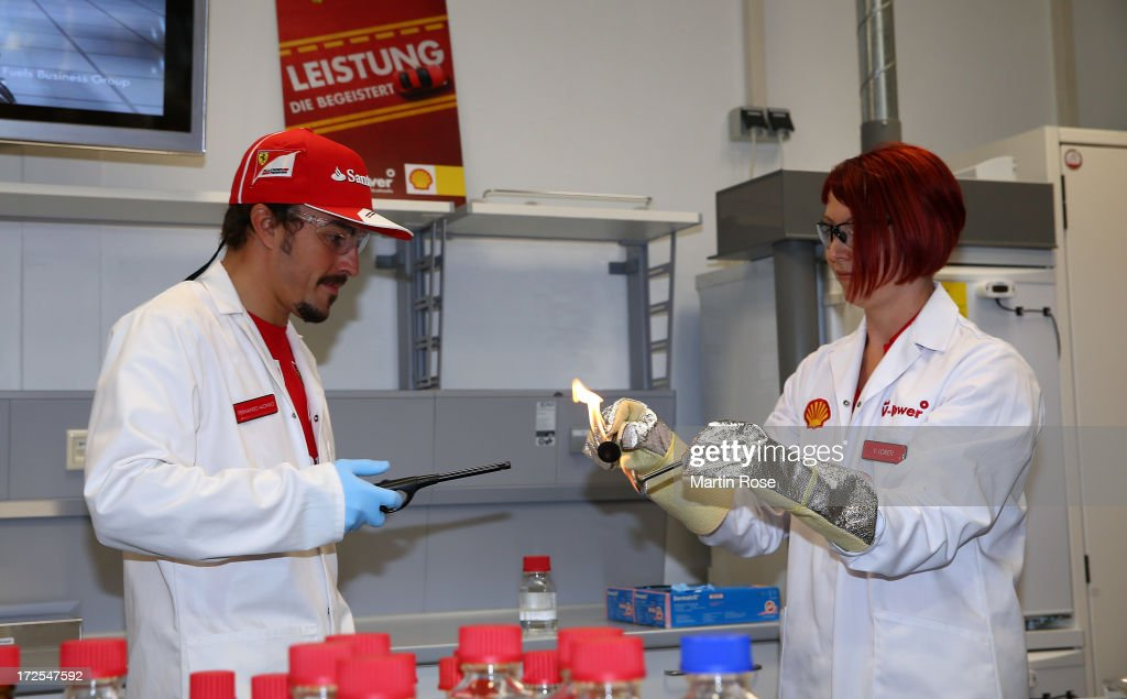 Ferrari driver Fernando Alonso (L) of Spain speaks to fuels scientist Valeria Loreti (R) during his visit of the german shell head quarter on July 3, 2013 in Hamburg, Germany.