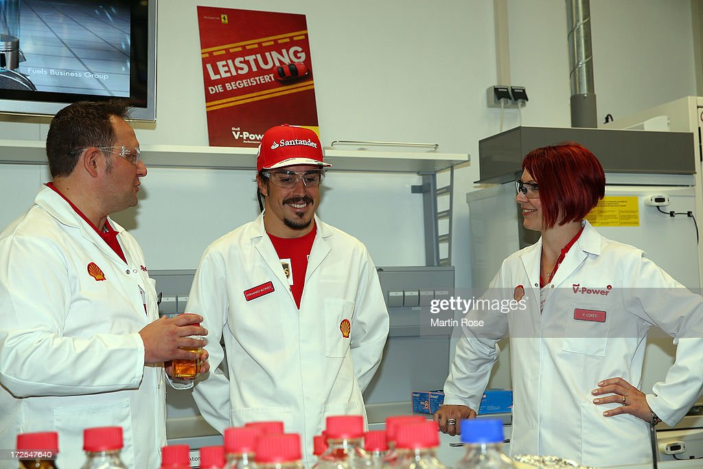 Ferrari driver Fernando Alonso (C) of Spain speaks to Jens Mueller Belau of Shell (L), global manager of fuels technology develepmont and fuels scientist Valeria Loreti (R) during his visit of the german shell head quarter on July 3, 2013 in Hamburg, Germany.