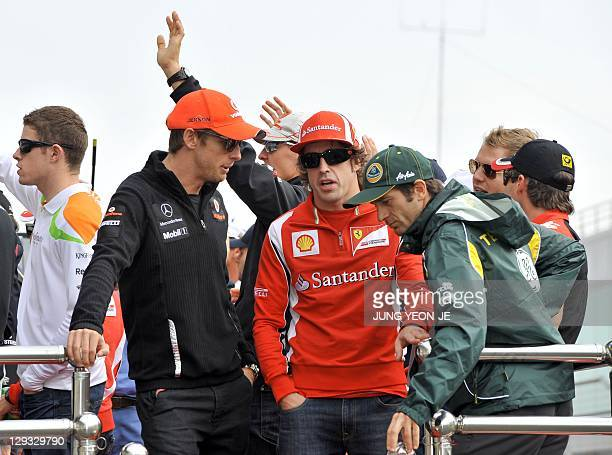 Ferrari driver Fernando Alonso of Spain walks with McLarenMercedes driver Jenson Button of Britain and Team Lotus driver Jarno Trulli of Italy as...