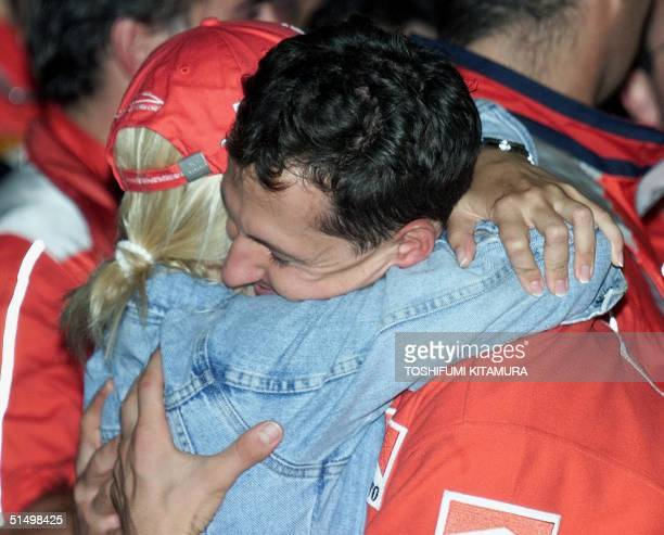 Ferrari driver Michael Schumacher of Germany hugs his wife Corinna in the pits to celebrate his victory in the Formula One Japanese Grand Prix as...