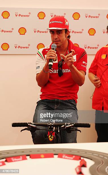 Ferrari drivers Fernando Alonso of Spain takes part in a pushbike challenge at the Backlot Studio during previews to the Australian Formula One Grand...