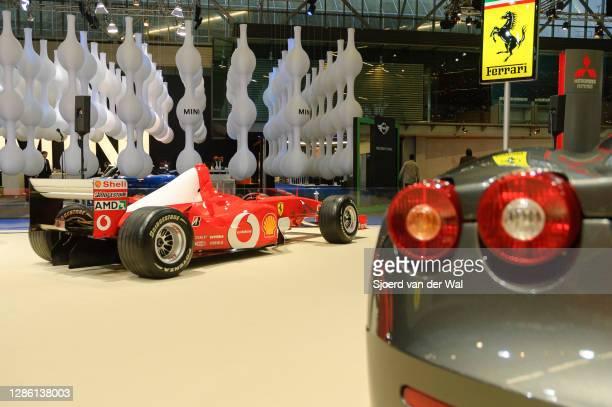 Ferrari F1 car behind the rear end of a Ferrari F430 sports car on display at Amsterdam motor show AutoRAI on February 9, 2005 in Amsterdam, The...