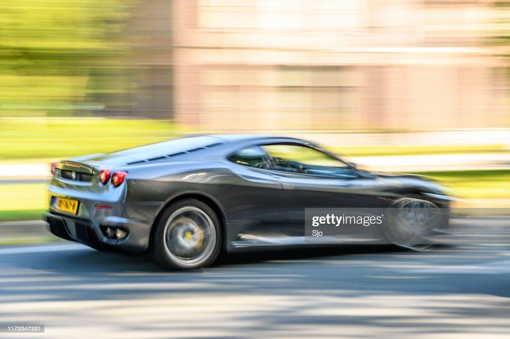 Ferrari F430 Italian sports car driving at high speed on a road : Stock Photo