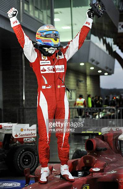 Ferrari Formula One driver Fernando Alonso stands on his car as he celebrates winning the South Korean Formula One Grand Prix at the Korean...