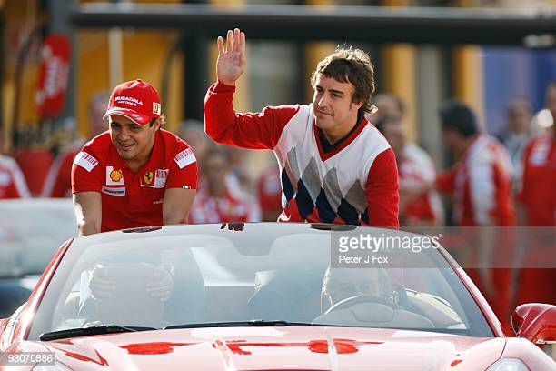 Ferrari Formula One Racing team drivers Felipe Massa of Brasil and Fernando Alonso of Spain and acknowledge fans as they are driven by Ferrari...