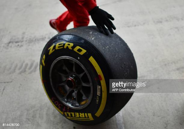 A Ferrari mechanic rolls a wheel along the pit lane during the second practice session at the Silverstone motor racing circuit in Silverstone central...