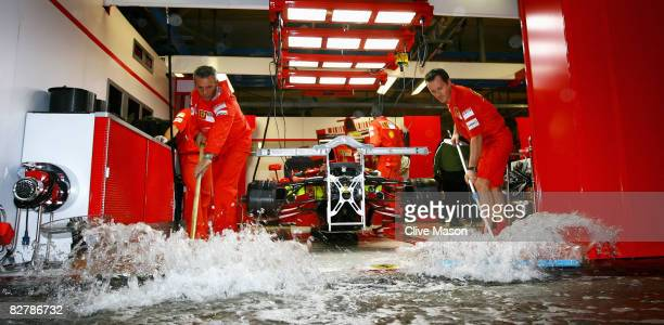 Ferrari mechanics clear rainwater from their garage as the pitlane becomes flooded during practice for the Italian Formula One Grand Prix at the...