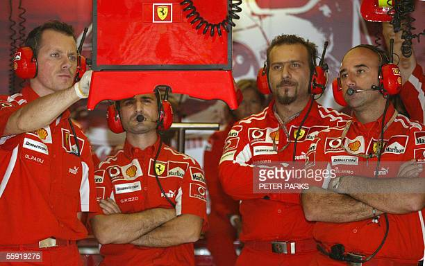 Ferrari mechanics look at the lap times of German Formula One driver Michael Schumacher in the Ferrari pit during the second free practise session of...