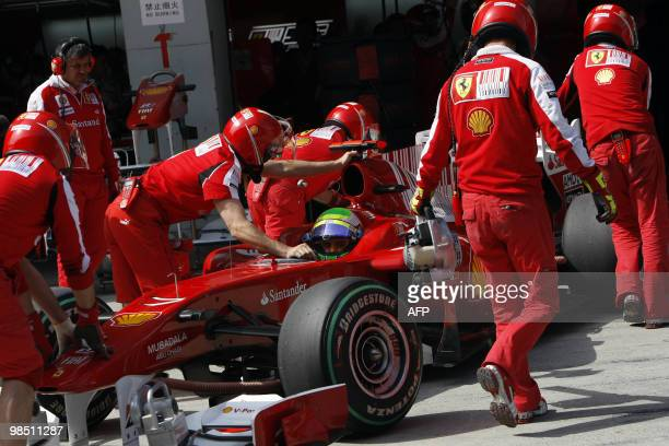 Ferrari mechanics push the car of Felipe Massa of Brazil during a pitstop for the third qualifying session for Formula One's Chinese Grand Prix in...