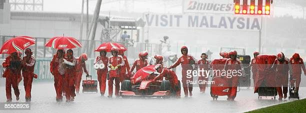 Ferrari mechanics shelter their car during heavy rain during the Malaysian Formula One Grand Prix at the Sepang Circuit on April 5 2009 in Kuala...