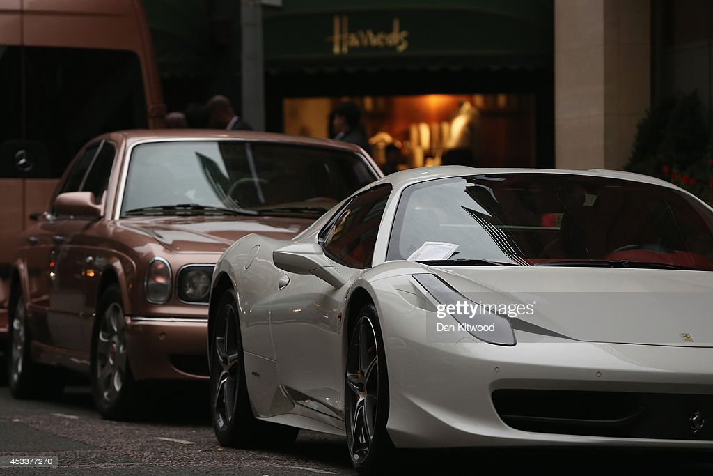 A Ferrari receives a parking ticket in Knightsbridge on August 8, 2014 in London, England. Tourists and car enthusiasts have been flocking to the wealthy London district to see some of the world's most expensive and extravagant super cars. Many of the rich owners from Saudi Arabia and Kuwait come to London to escape the summer heat at home and to show off their cars before moving on to other European cities such as Paris and Cannes.