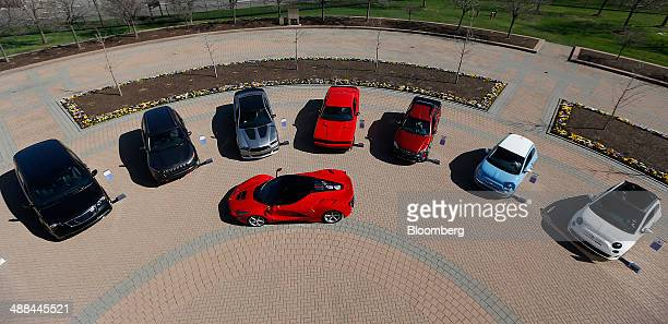 A Ferrari SpA LaFerrari vehicle front center is surrounded by Chrysler Group LLC Town and Country Jeep Cherokee Dodge Challenger Dodge Charger Fiat...