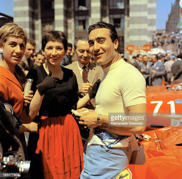 Ferrari team leader Eugenio Castellotti chats with two ladies during scrutineering in the Piazza Vittoria in Brescia Italy before the start of the...