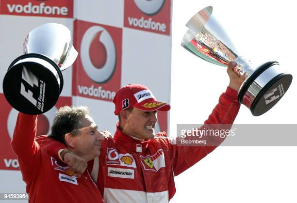 Ferrari team manager Jean Todt, left, and winner Michael Schumacher celebrate their victory on the podium at the Formula 1 GP of Italy in Monza,...