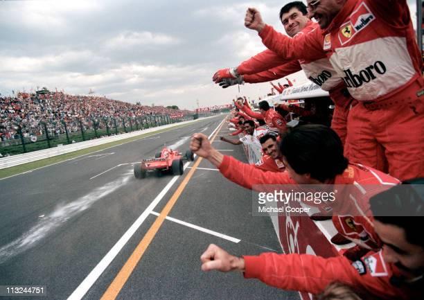 Ferrari team mechanics celebrate on the pit wall as Michael Schumacher drives the Scuderia Ferrari Marlboro Ferrari F310Bacross the line to win the...