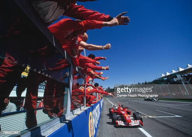 Ferrari team members salute Michael Schumacher from the pit lane wall as he drives the Scuderia Ferrari Marlboro Ferrari F2004 Ferrari V10 to win the...