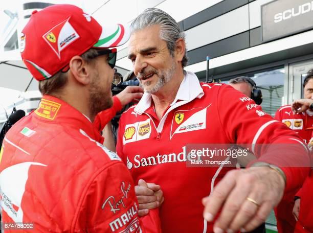 Ferrari Team Principal Maurizio Arrivabene congratulates pole sitter Sebastian Vettel of Germany and Ferrari in the Paddock during qualifying for the...