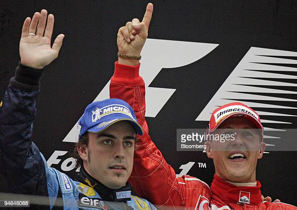 Ferrari team's Michael Schumacher of Germany, right, and Renault team's Fernando Alonso of Spain, left, wave to the crowd after Schumacher won the...
