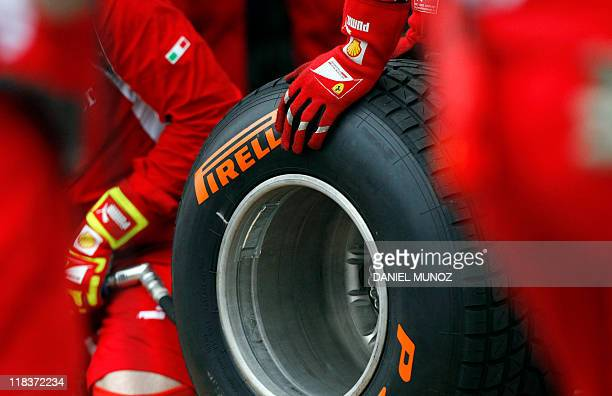 Ferrari technicians handle a Pirelli wet tyre during qualifying session for Formula One's Australian Grand Prix at the Albert Park circuit in...