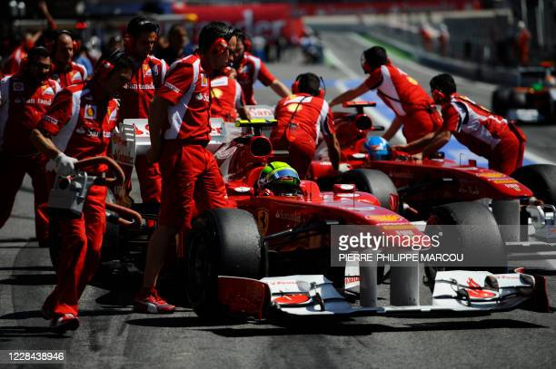 Ferrari's Brazilian driver Felipe Massa and Ferrari's Spanish driver Fernando Alonso are assisted in the pits at the Circuit de Catalunya on May 20,...