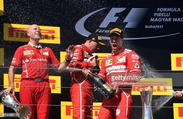 Ferrari's engineer Jock Clear secondplaced Ferrari's Finnish driver Kimi Raikkonen and winner Ferrari's German driver Sebastian Vettel celebrate on...