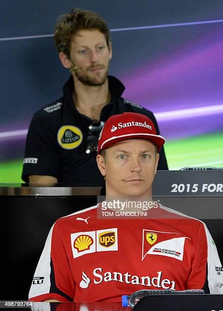 Ferrari's Finnish driver Kimi Raikkonen and Lotus F1 Team's French driver Romain Grosjean sit during the press conference at the Yas Marina circuit...
