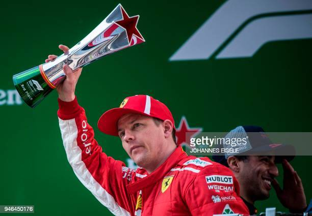 Ferrari's Finnish driver Kimi Raikkonen celebrates on the podium after placing third in the Formula One Chinese Grand Prix in Shanghai on April 15...