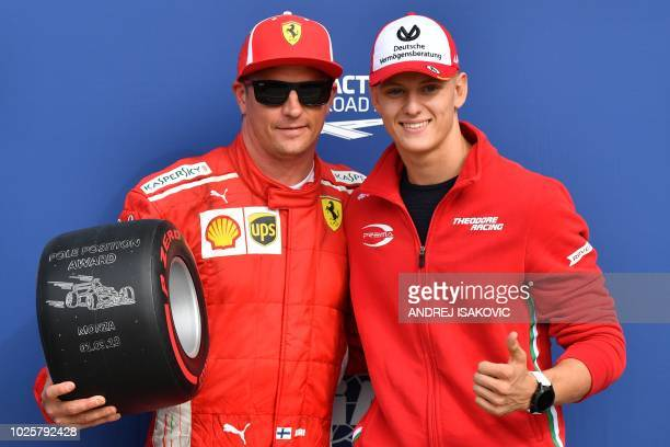 Ferrari's Finnish driver Kimi Raikkonen celebrates winning the pole position and holds the Pirelli Pole Position Award as he poses with Mick...