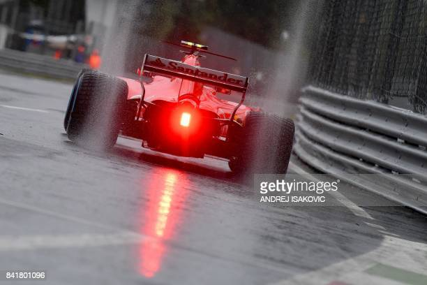 TOPSHOT Ferrari's Finnish driver Kimi Raikkonen drives on a wet circuit during the third practice session at the Autodromo Nazionale circuit in Monza...