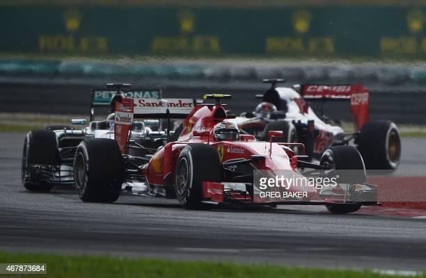 Ferrari's Finnish driver Kimi Raikkonen leads Mercedes AMG Petronas F1 Team's British driver Lewis Hamilton on the last dry lap before rain delayed...