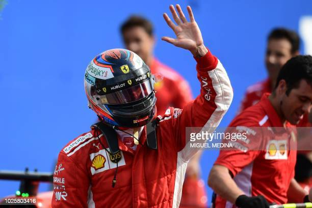 Ferrari's Finnish driver Kimi Raikkonen waves to the crowd as he celebrates winning the pole position after the qualifying session at the Autodromo...